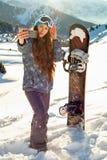 Snowboarder девушки стоя на верхней части горы на заходе солнца и делая selfie Стоковые Фотографии RF