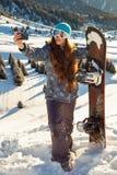 Snowboarder девушки стоя на верхней части горы на заходе солнца и делая selfie Стоковая Фотография