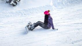 Snowboarder девушки упал и сидящ на снеге Стоковые Фотографии RF
