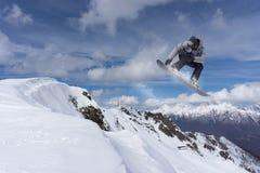 Snowboarder летания на горах весьма спорт Стоковое Изображение
