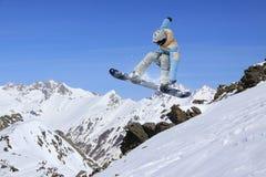 Snowboarder летания на горах весьма спорт Стоковая Фотография
