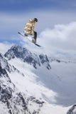 Snowboarder летания на горах весьма спорт Стоковая Фотография RF