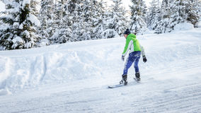 Snowboarder едет сноуборд на наклоне лыжи Стоковая Фотография