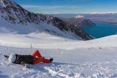 Snowboarder женщины кладя на снег и наслаждается солнечным светом Стоковые Фотографии RF