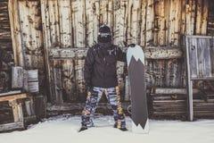 Snowboarder нося черную куртку, маску с домом конца сноуборда подлинным деревянным горизонтально Стоковое Изображение RF
