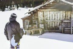Snowboarder нося черную куртку, маску с домом конца сноуборда подлинным деревянным Человек идя с столом доски снега Стоковое фото RF