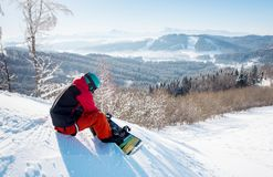 Snowboarder отдыхая в горах Стоковые Изображения RF