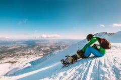 Snowboarder прикрепляет пряжки сноуборда сидя на верхней части холма снега Стоковые Изображения