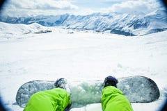 Snowboarder сидя дальше ослабляет момент в горе Стоковые Фото