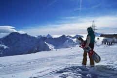 Snowboarder стоя с сноубордом в горах Стоковые Фото
