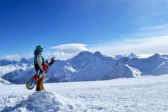 Snowboarder стоя с сноубордом в горах Стоковая Фотография RF