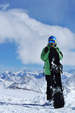 Snowboarder стоя с сноубордом в горах Стоковые Изображения RF