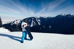 Snowboarder с сноубордом на верхней части горы зимы Стоковое Изображение