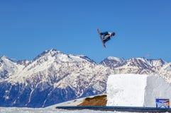 Snowboarder человека летает фристайл от скачки на предпосылке горного пика Chugush и голубого неба Сочи, Кавказ стоковое изображение rf