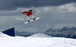 Snowboarder. Is jumping over the mountains Royalty Free Stock Photo