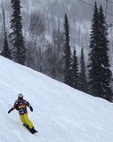 Snowboarder. Rides down the mountain slope Stock Image