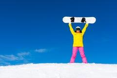 Το κορίτσι Snowboarder που ανατρέφεται λαβή οπλίζει τη μόνιμη Στοκ φωτογραφία με δικαίωμα ελεύθερης χρήσης