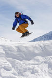 Snowboarder. Taking a jump in fresh snow Stock Photography