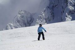 Snowboarder abwärts auf schneebedeckter Skisteigung im hohen Berg Lizenzfreie Stockfotos