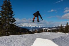 Snowboarder in Action: Jumping in the Mountain Snowpark.  Royalty Free Stock Image