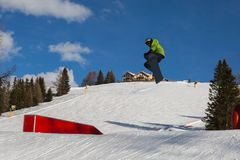 Snowboarder in Action: Jumping in the Mountain Snowpark.  Stock Photo