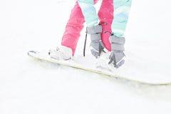 Snowboarder adjusting bindings Royalty Free Stock Photo
