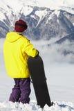 Snowboarder adolescente que admira Mountain View Foto de archivo libre de regalías