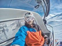 Snowboarder all'elevatore nel giorno soleggiato delle montagne delle alpi Fotografia Stock