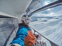 Snowboarder all'elevatore nel giorno soleggiato delle montagne delle alpi Fotografie Stock