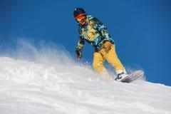 Snowboarder ativo no sportswear brilhante que monta abaixo de uma inclinação de montanha do pó imagem de stock