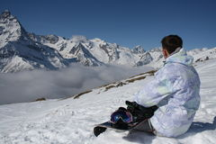 Snowboarder on a background of mountains. The man with the snowboard sits on the edge of the slope Stock Photo