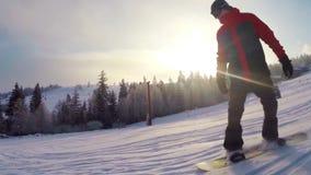 Snowboarder beklimt onderaan een berg stock video