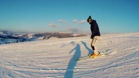 Snowboarder beklimt onderaan een berg stock footage