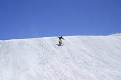 Snowboarder bergaf in terreinpark bij de skitoevlucht bij de zonwinter Stock Afbeelding