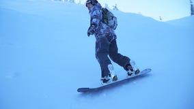 Snowboarder berijdt voorbij de camera op een snow-covered helling stock videobeelden