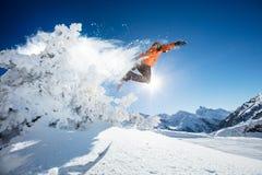 Snowboarder bij sprong in Alpiene bergen stock afbeelding