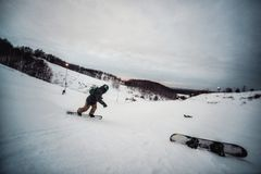 Snowboarder in a black helmet riding on a snowy track. stock images