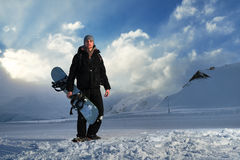 Snowboarder in black suit standing on the road Royalty Free Stock Images