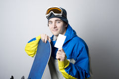 Snowboarder with blank lift pass. Young male Snowboarder holding blank ski lift pass leaning on Snowboard looking at camera. Concept to illustrate ski admission Stock Image