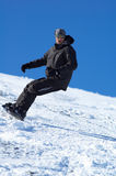 Snowboarder and blue sky. Snowboarder downhill Stock Photography