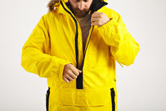 Snowboarder in bright anorak. Serious bearded young man zipping up his bright yellow warm snowboarding anorak isolated on white royalty free stock images