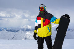 Snowboarder carries a board in  hands. Stock Image