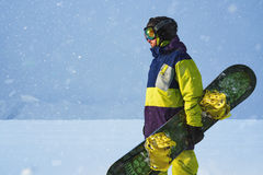 Snowboarder carries a board in  hands. Evening snowfall in  mountains. Royalty Free Stock Photos