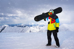 Snowboarder carries a snowboard in hand. Royalty Free Stock Photos