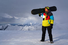 Snowboarder carries a snowboard in hand. Stock Image
