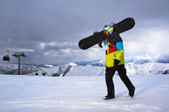 Snowboarder carries a snowboard in hand. Royalty Free Stock Photography