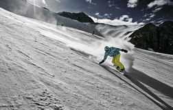 Snowboarder in a carved turn. Snowboarder touches the slope in a turn stock photography