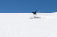 Snowboarder carving a turn on a blue sky day. Royalty Free Stock Photos