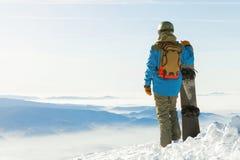 Snowboarder in casco che sta alla cima di una montagna all'ora dorata e che tiene il suo snowboard con una mano Fotografie Stock