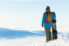 Snowboarder in casco che sta alla cima stessa di una montagna e che tiene il suo snowboard con una mano Immagine Stock Libera da Diritti
